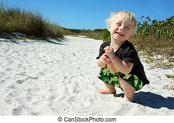 Laughing Child Playing in Sand at Beach