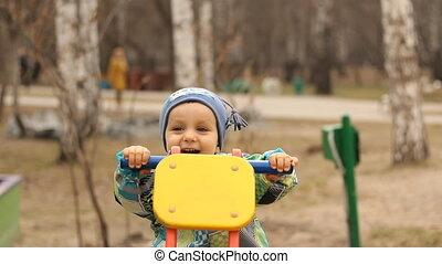 Laughing Child rocking on a rocker