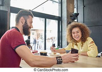 Laughing couple eating cake, drinking coffee, looking at smartphone.