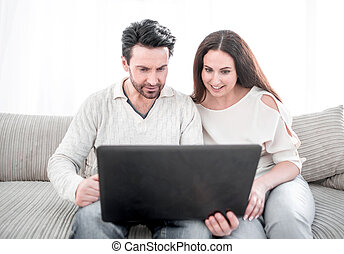 laughing couple looking at the laptop screen.