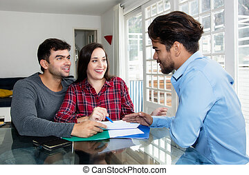 Laughing couple signing contract for own house