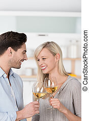 Laughing couple toasting with white wine