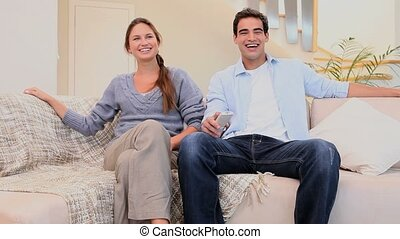 Laughing couple watching television