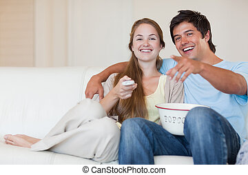 Laughing couple watching television while eating popcorn