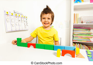 Laughing cute boy putting blocks in sequence by memory in...