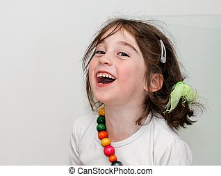 Laughing cute girl in white shirt with colored beads