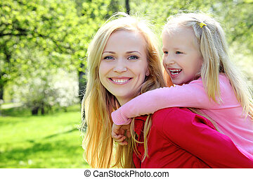 laughing daughter sits at mother on back in spring park