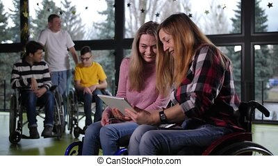 Laughing disabled women in wheelchair using tablet