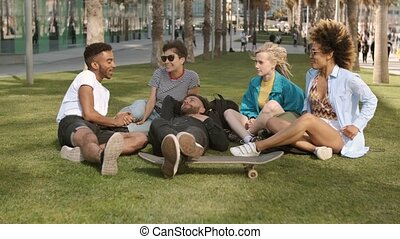 Laughing diverse friends chilling in park - Group of modern...