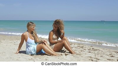 Laughing diverse women chilling on beach - Two multiracial...