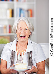 Laughing elderly woman holding a birthday cake with burning...