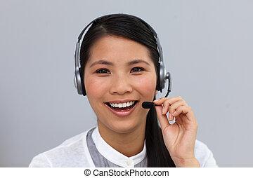 Laughing ethnic businesswoman using headset