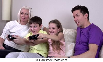 Laughing family playing video games in a living room,...