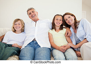 Laughing family sitting on the couch