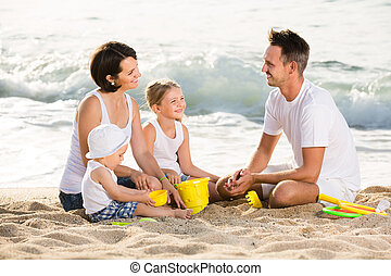 Laughing family with children playing at beach
