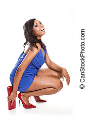 Laughing fashionable African woman in a short blue dress...