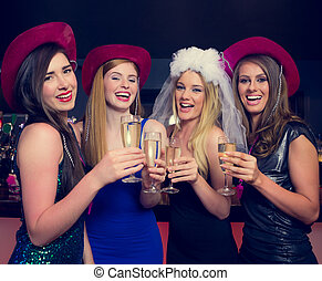 Laughing friends clinking champagne glasses at a hen night...