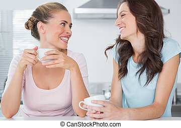Laughing friends having cup of coffee