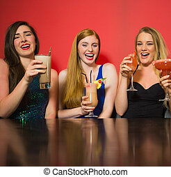 Laughing friends holding cocktails