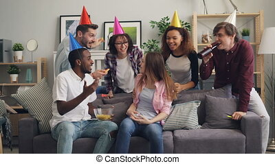 Laughing friends in party hat congratulating girl on...