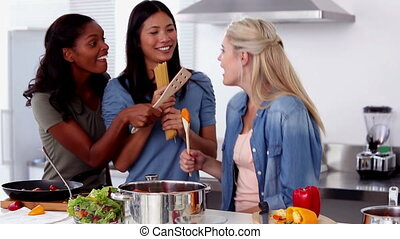 Laughing friends singing into a wooden spoon while cooking...