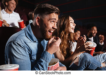 Laughing friends sitting in cinema watch film - Image of...