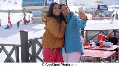 Laughing friends taking a selfie at a ski resort