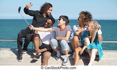 Laughing friends taking selfie on seafront - Laughing young...