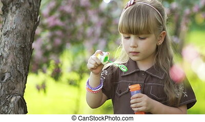 Laughing girl blowing bubbles