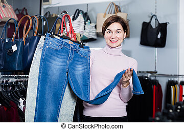 Laughing girl deciding on new jeans