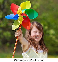 laughing girl holding colorful windmill - laughing girl...