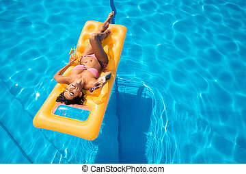 Laughing girl lying on air mattress - Laughing young girl...