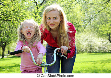laughing girl on bicycle with mother in spring garden