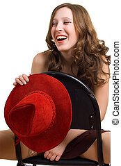 Laughing girl with a red hat sits astride on a chair