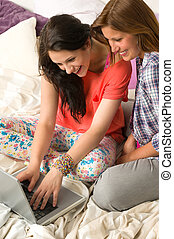 Laughing girls chatting with friends online
