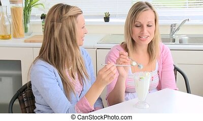 laughing girls eating ice-cream at home