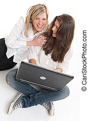 Laughing girls with laptop