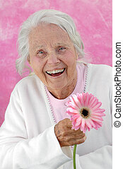 Laughing great grandmother with a pink Gerbera flower, photographed on a pink background. Woman in her eighties.
