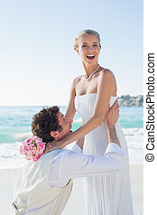 Laughing groom picking up his pretty blonde wife smiling at camera at the beach