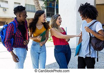 Laughing group of international students walking to university