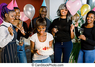 Laughing group of young african friends celebrating together birthday of an attractive young African woman which holds a cake with candles in her hands