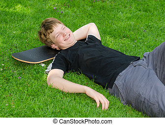 Laughing guy relax on skateboard in park grass