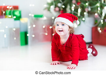 Laughing happy baby girl in a red dress and santa hat playing be