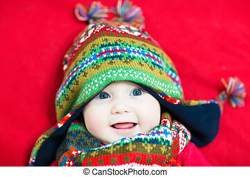 Laughing happy baby in a colorful knitted hat and scarf