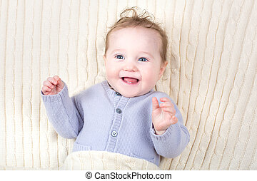Laughing happy baby in a knitted blanket