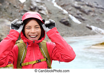 Laughing happy woman hiking with backpack in rain