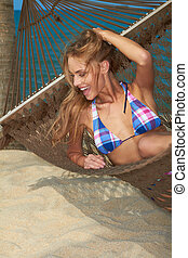 Laughing happy woman reclining in a hammock