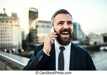Laughing hipster businessman with smartphone in the city, making a phone call.