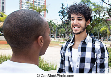 Laughing hipster man talking with african american friend