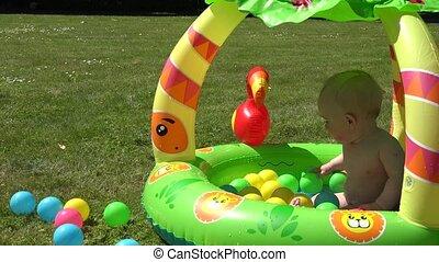 Laughing infant baby splash water in pool full of colorful balls. 4K